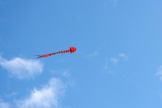 비행 연. 구름 사이로 푸른 하늘에 바람에 날리는 화려한 연. 붉은 용의 형태를 한 긴 뱀