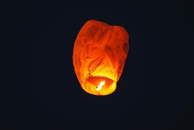 暗い空に飛んでいるランタン