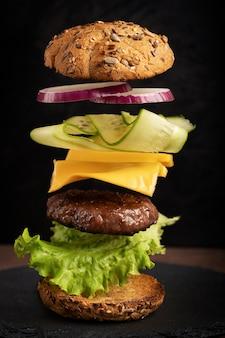 ハンバーガーとビーフミート、チーズ、キュウリ、オニオンリングのフライングレイヤーを暗闇に照らして