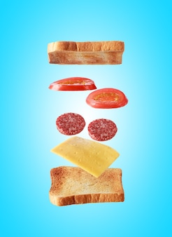 Летающие слои бутерброда с тостами, салями, сыром и овощами на синем фоне. концепция питания для завтрака