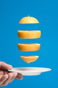 Летающие дольки лимона над белым блюдцем. синий фон.