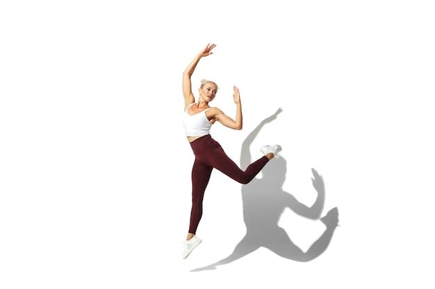 蝶のように飛んでいる白いスタジオの背景のpotraitで練習している美しい若い女性アスリート