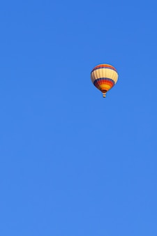 Flying multicolored balloon in the bright blue sky