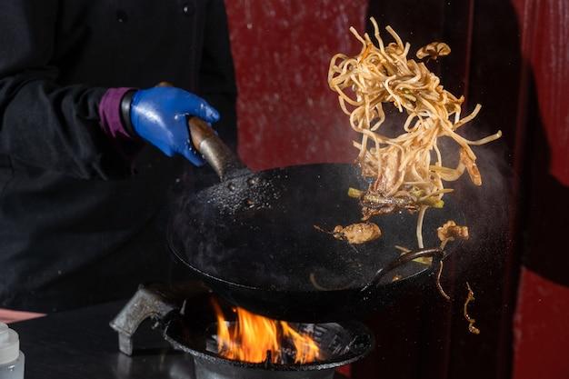 고기가 든 냄비 상자 용 날아 다니는 국수, 냄비 냄비에 튀긴 간장, 길거리 음식. 프리미엄 사진