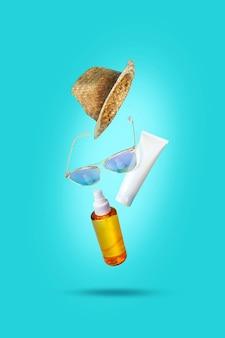 飛んでいる物、日焼け止め。帽子、サングラス、オイル、クリーム。コンセプト夏休み、ミニマリズム