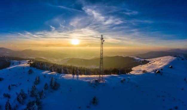 산에 있는 라디오 타워 위로 날아가는 눈 덮인 겨울 풍경.