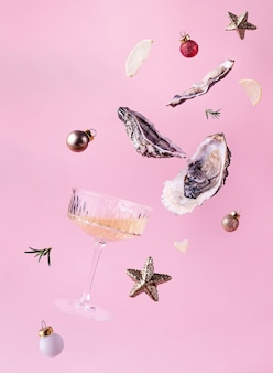 Flying oysters, glass of wine and christmas balls on a pink background. festive christmas or new year creative concept.