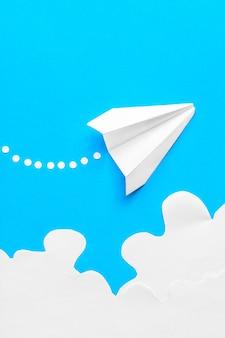 雲の中で飛ぶ紙飛行機。飛行、旅行、乗り換えの概念