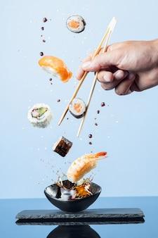 Летающие кусочки суши на синем фоне. вертикальный формат.