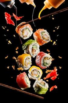 Летающие кусочки суши с деревянными палочками и соусом