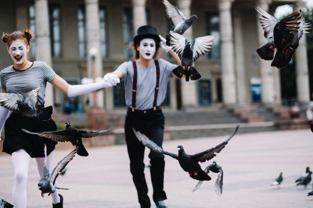Flying pigeons in front of mime couple running