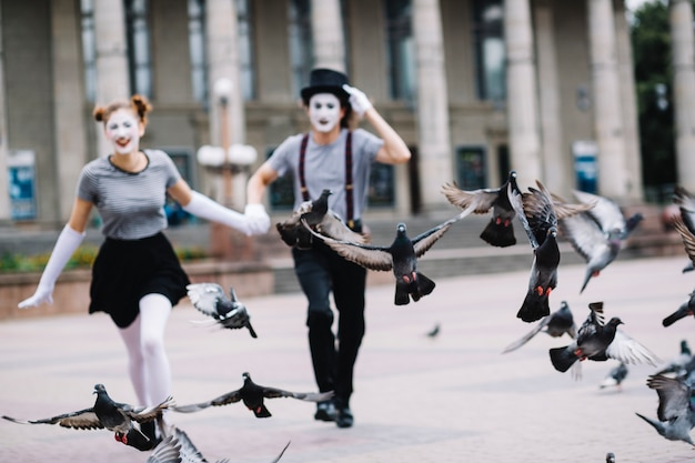 Flying pigeons near running mime couple
