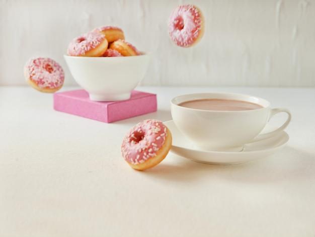 흰색 바탕에 카카오 한 잔과 함께 날아다니는 분홍색 도넛. 달콤한 핑크 플라잉 도넛, 맛있는 정크 푸드 개념에 대한 선택적 초점