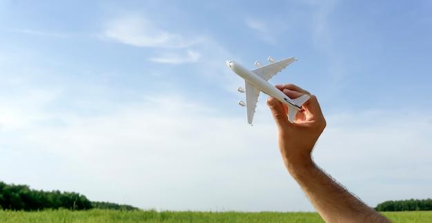 青空バナーの背景に飛んでいる飛行機。手に持ったおもちゃの飛行機が飛んで行きます。夏、休暇、旅行、リラクゼーション、ツアー、フライトのコンセプト。高品質の写真