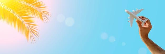 Летающий самолет на фоне баннера голубого неба и тропических листьев. в путешествие летит игрушечный самолетик в руках. лето, отдых, путешествия, релаксация, туры и концепция полетов. фото высокого качества