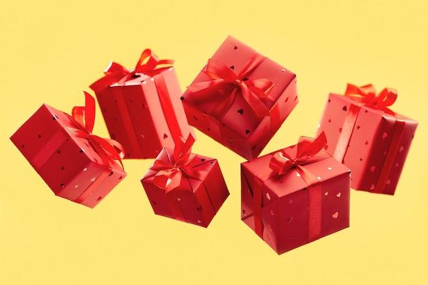 노란색 표면에 선물을 가진 빨간 상자를 비행