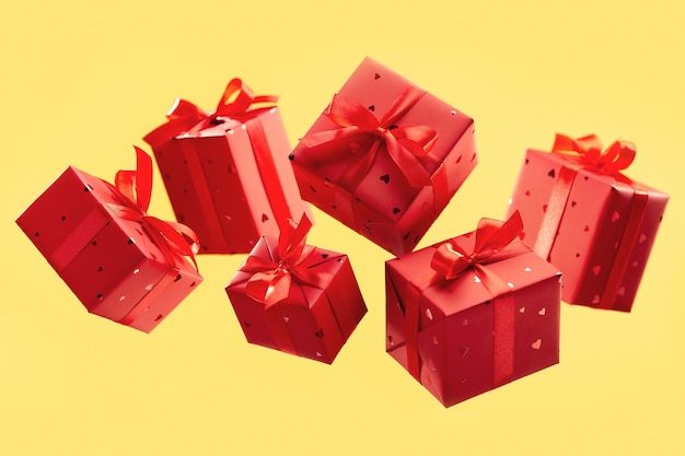 Flying red boxes with gifts on yellow surface