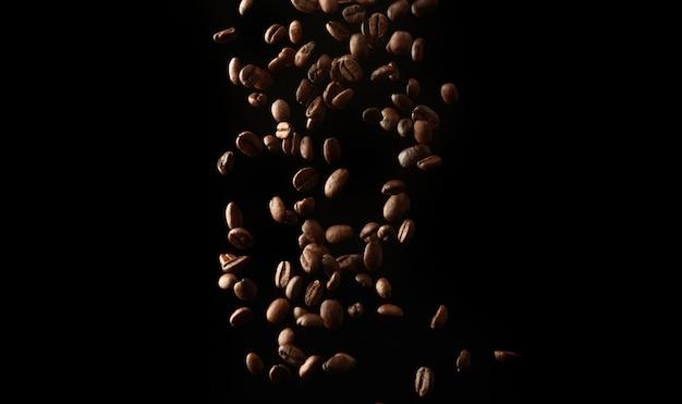 黒い背景にローストコーヒーの穀物を飛んでください。