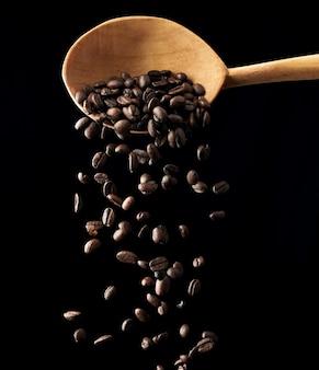 黒い空間にローストコーヒーの穀物を飛んでください。