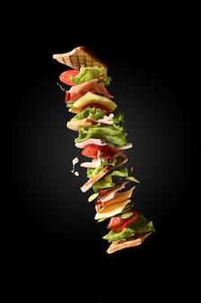 暗い背景にフライングサンドイッチ。クリエイティブなコンセプト。