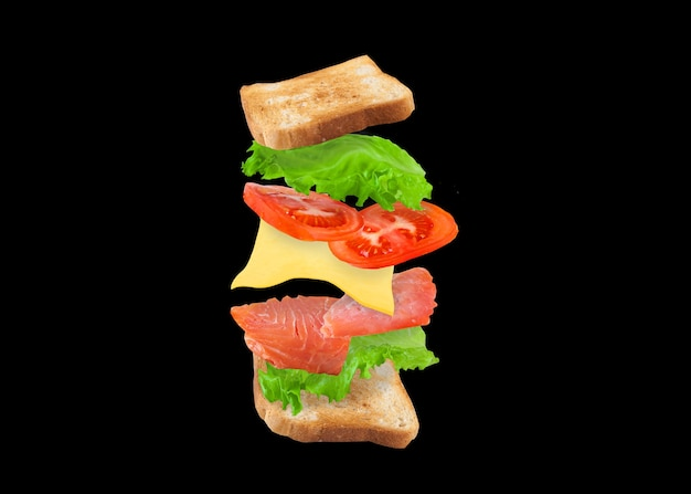 Flying sandwich with salmon, cheese and tomatoes on a black.