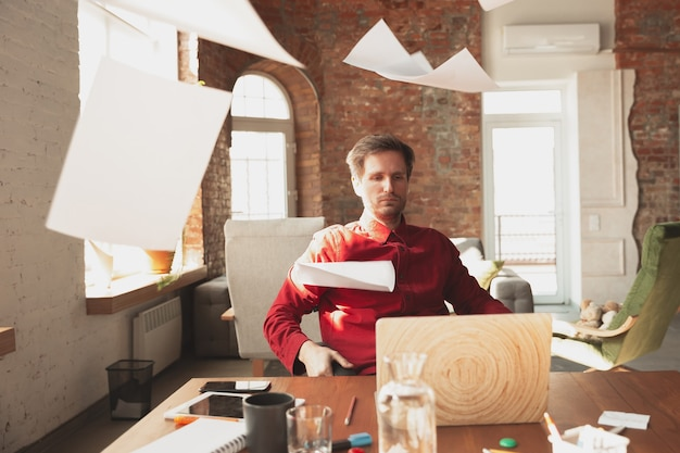 Flying sheets. caucasian entrepreneur, businessman, manager trying to work in office. looks funny, lazy, spending time. concept of work, finance, business, success and leadership. deadline, hurry up
