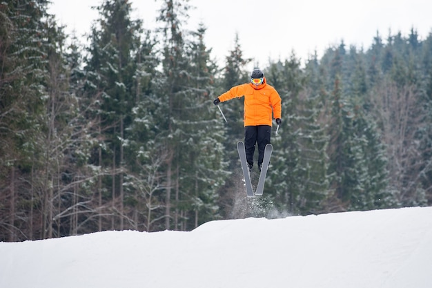Flying skier at jump from the slope of mountains
