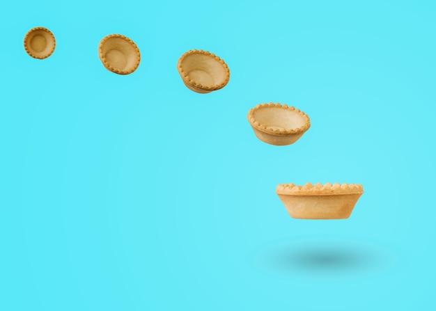 青い表面に飛んでいるスナックケーキ。おやつ用の焼き菓子。