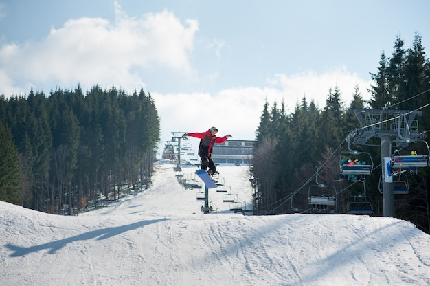 Flying snowboarder at jump from the slope of mountains