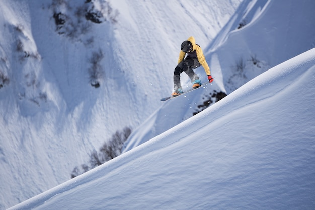 Flying snowboarder on mountains.