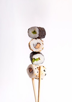 Flying sushi on a white background, tasty sushi rolls, avocado and chopsticks
