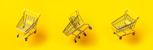 Flying three empty trolleys on a bright yellow background. close-up. banner.