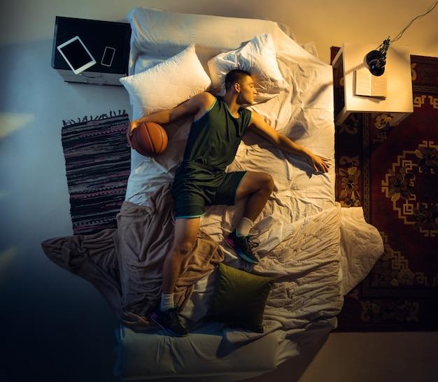 Летающий. вид сверху молодого профессионального баскетболиста, спящего в своей спальне в спортивной одежде с мячом. любить спорт даже больше, чем комфорт, играть в матче, даже если отдыхает. действие, движение, юмор.