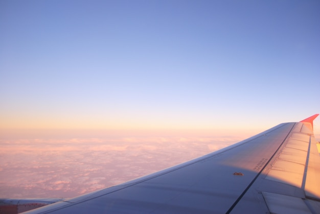 Flying and traveling, view from airplane window on the wing on sunset time