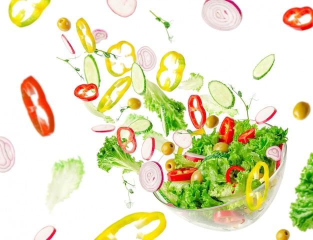 Ингридиенты летающего салата над прозрачной миской. витамины и концепция здорового питания.