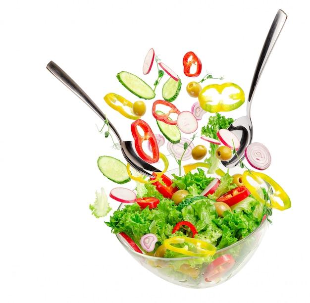 Ингридиенты летающего овощного салата над прозрачной миской с ложками. концепция здорового сбалансированного питания.