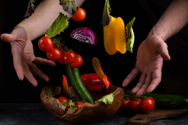 男性の手の間にサラダ用野菜を飛ばします。健康的なベジタリアン料理は浮揚
