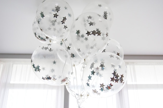 Flying white balloons with silver stars under the ceiling