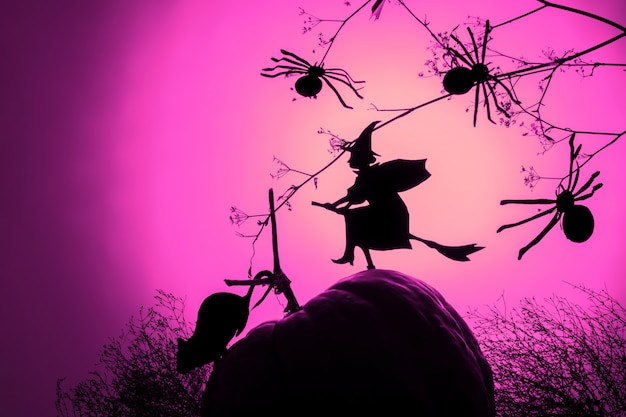 A flying witch silhouette and spiders of black paper on pink gradient