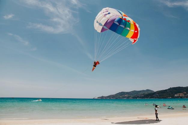 タイの夏の晴れた日にビーチでパラグライドで飛んでいます。