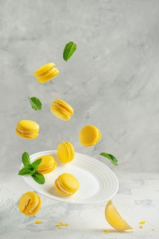 Flying yellow citrus macaroons with mint leaves on white plate