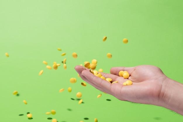 緑の背景の前に手から黄色い錠剤を飛んで