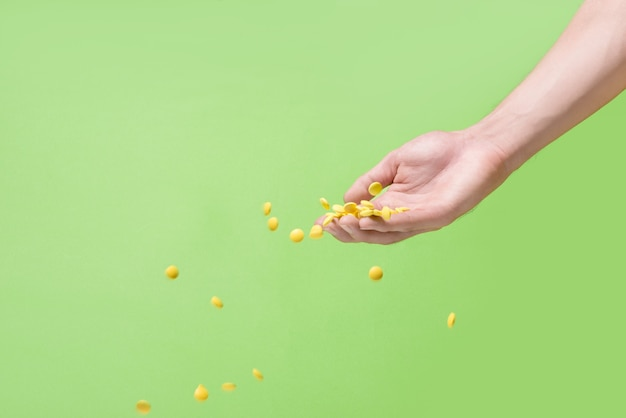 녹색 배경 앞에서 손에서 날아가는 노란색 알약