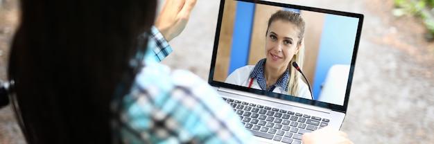 車椅子の女性障害者が美容師とオンラインで話します。オンラインリハビリテーションコンセプトを支援