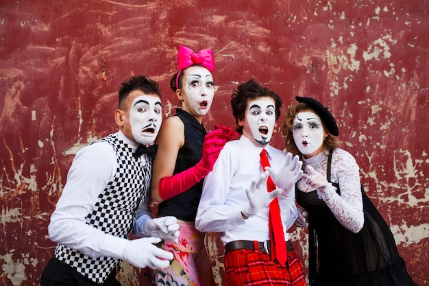 Fmimes standing on a red wall