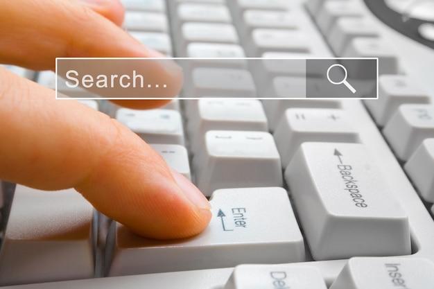 Fnger가 중앙에 검색 창이있는 컴퓨터 키 enter를 누릅니다.