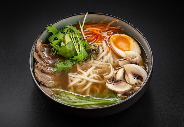 黒い表面に肉、ニンジン、卵が入ったfo-boスープ