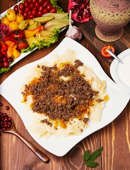 白人の伝統的なfoのkhingal、ヒンカリ語。木製のテーブルの上の白い皿に肉と白人のパスタ。