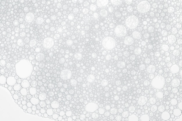Foam bubbles from soap or shampoo washing on white background.