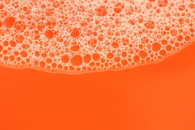 Пена крупным планом пузыри на ярко-оранжевом фоне. апельсиновая мыльная пена